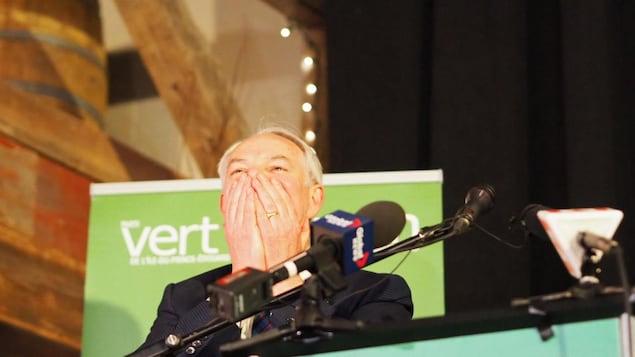 Peter Bevan-Baker se couvre la bouche des mains, heureux d'avoir remporté un siège.