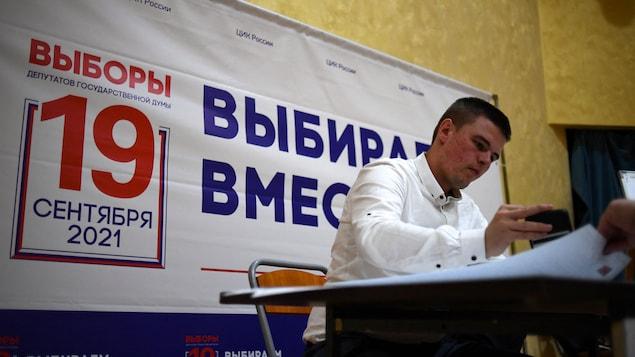 Un membre d'un bureau électoral russe regarde une série de documents sur un bureau, avec une affiche électorale derrière lui.