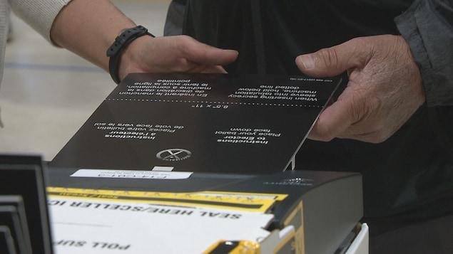 Un homme dépose son bulletin de vote dans une tabulatrice