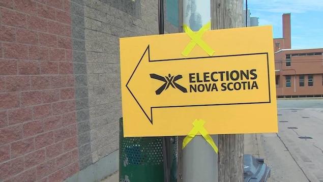 Affiche jaune d'Élections Nouvelle-Écosse avec une flèche pointant vers un bureau de vote.