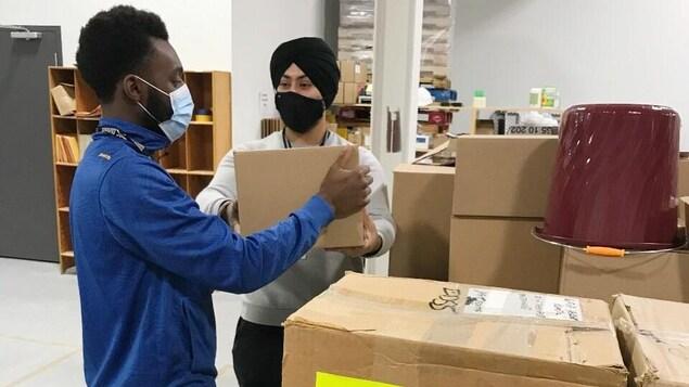 Des travailleurs d'Élections Nouvelle-Écosse dans un entrepôt à Dartmouth.