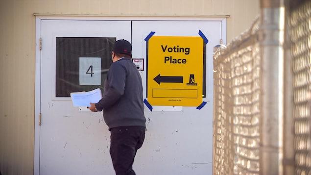 Un homme qui s'en va voter est en train d'ouvrir la porte.