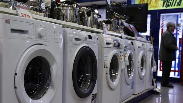 Un homme à côté de machines à laver à l'intérieur d'un magasin d'électroménager