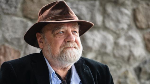 Serge Bouchard portant son éternel chapeau regarde au loin.