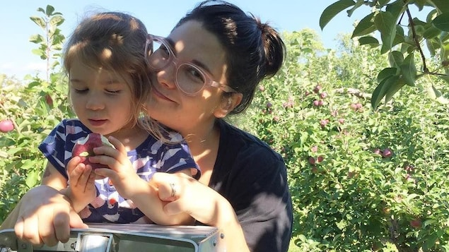 L'écrivaine Érika Soucy, cofondatrice du nouvel événement Électrons Livres. Un jeune femme dans la trentaine avec sa petite fille dans un verger.