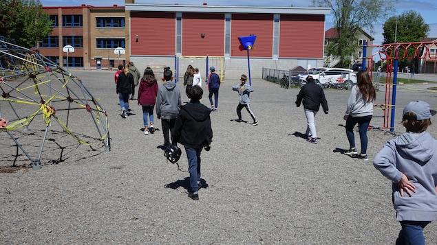 Des élèves tentent de garder une distance de deux mètres entre eux en marchant à la queue leu leu vers l'école.