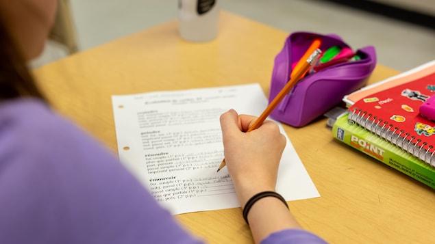 Une élève écrit sur une feuille des verbes.