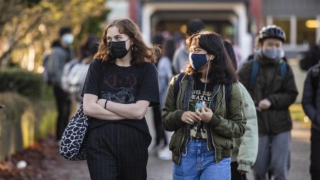 Des étudiants marchent à la sortie des classes et portent un masque contre la COVID-19.