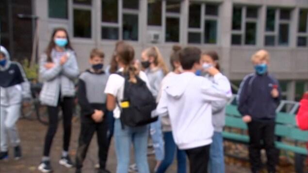 Une image floue d'élèves devant un bâtiment. Ils portent leur masque.