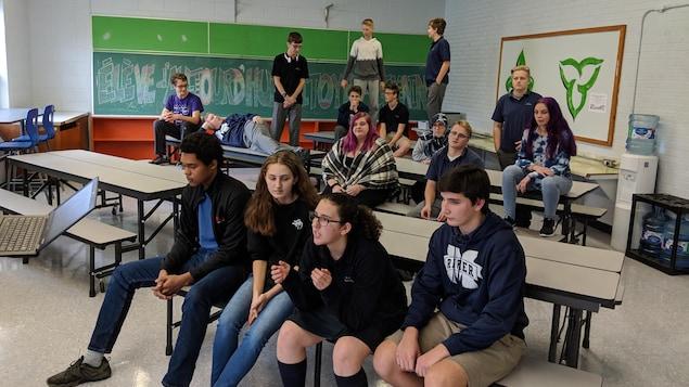Des élèves dans une salle de classe assis et debout sur des tables.