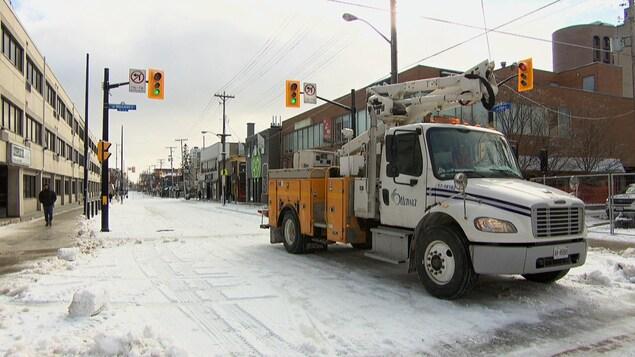 Un camion municipal franchit une intersection.