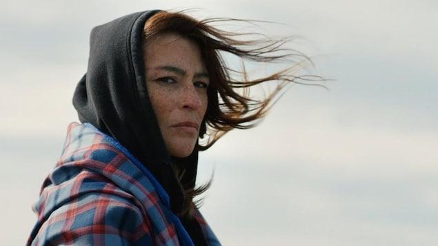 Elisapie portant un chandail à capuchon noir et regardant au loin en ayant les cheveux au vent.