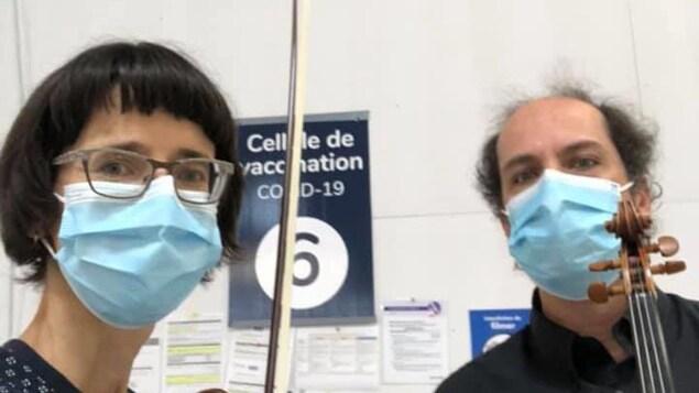 Selfie d'Élise Lavoie et Hugues Laforte Bouchard avec leurs instruments de musique et leurs masques de procédure au visage.