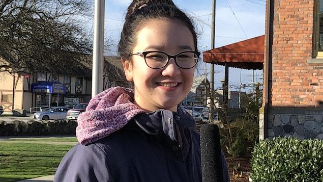 Une jeune femme sourit avec un micro à la main devant un édifice par une journée ensoleillée.