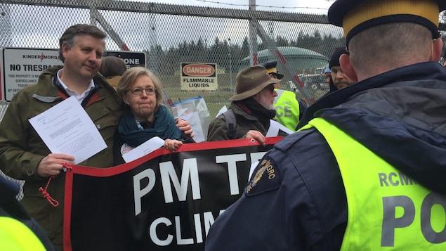 Un homme et une femme qu'il tient par l'épaule, ainsi que d'autres personnes sont entourés par des policiers.