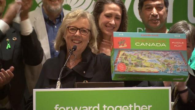 Elizabeth May, souriante, brandit un casse-tête reproduisant schématiquement le Canada.