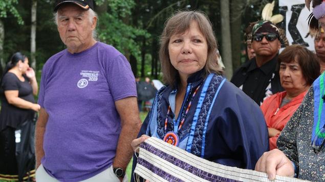 Ellen Gabriel, entourée d'aînés, tient un Wampum.