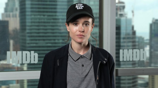 Elliot Page porte une casquette noire et un chandail gris.