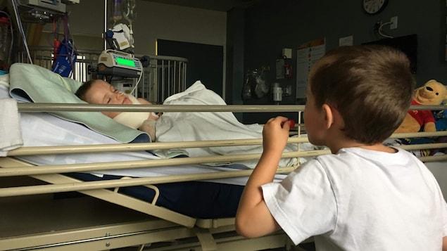 Un jeune garçon est étendu dans un lit d'hôpital alors que son frère jumeau est à ses côtés.