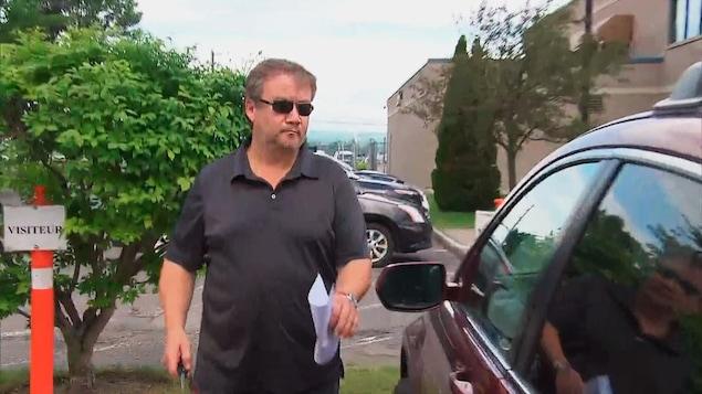 Éloi Bossé se dirige vers sa voiture, un papier à la main.