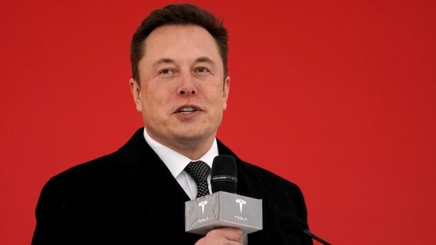 Un homme parle au micro devant un mur rouge