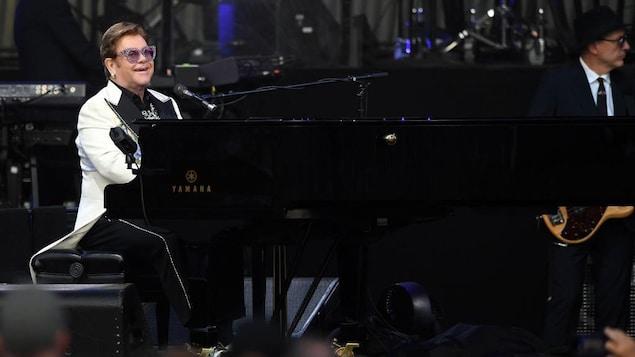 Elton John joue du piano et sourit.