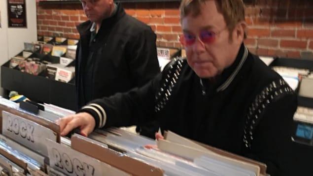 Le chanteur britannique sir Elton John et son garde du corps dans le magasin de disques Beat Street Records au centre-ville de Vancouver le 9 mars 2017