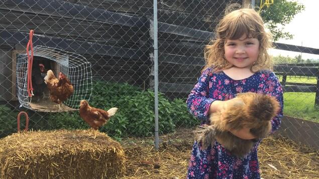 Elyse, 4 ans, pose fièrement avec sa poule préférée.