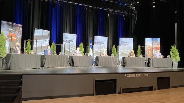 Plusieurs tables où des dignitaires sont assis au moment de la conférence de presse.