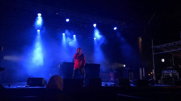 Un homme chante au micro sur une scène en soirée.