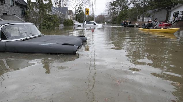 Deux embarcations passent devant des véhicules submergés sur une rue de Sainte-Marthe-sur-le-Lac.