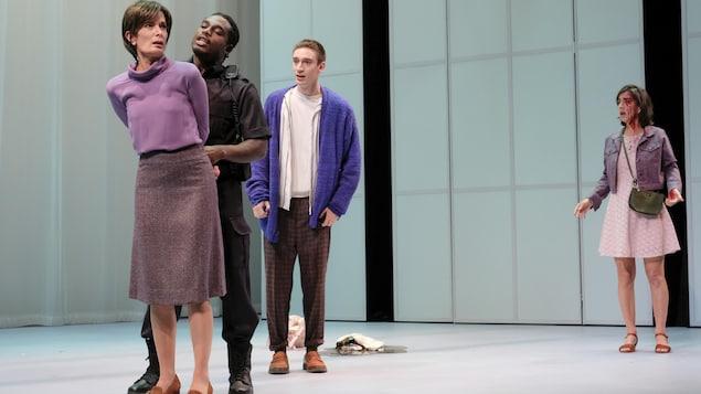 Quatre personnes sont sur la scène et l'une tient une femme par les mains, derrière son dos.