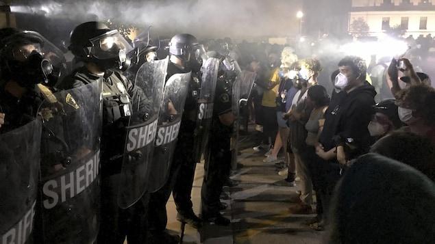 Des membres de l'antiémeute font face à des manifestants dans la nuit.