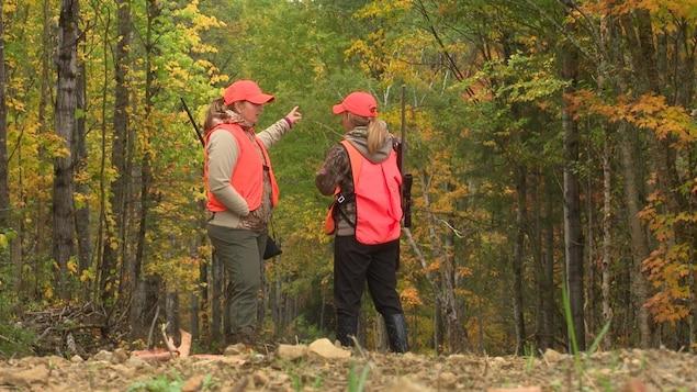 Deux chasseuses dans les bois,  vêtues d'habits de chasse.
