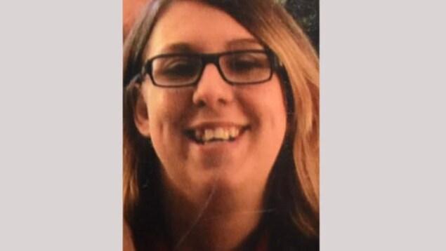 Une jeune femme portant des lunettes sourit.