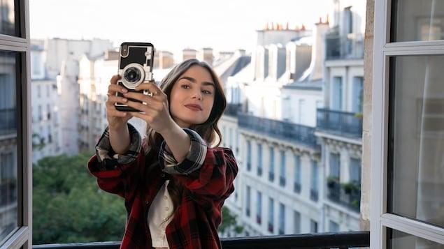 La comédienne prend un égoportrait devant le cadre d'une fenêtre donnant sur le quartier Montmartre, à Paris.