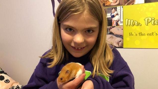 Une jeune fille tient un hamster bicolore dans ses mains.