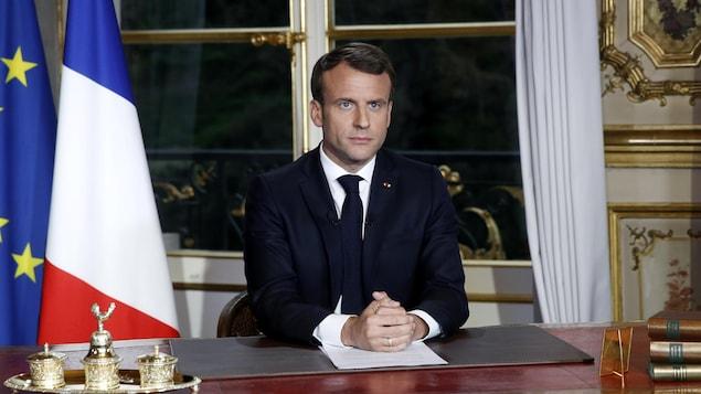 Emmanuel Macron à son bureau de l'Élysée, des drapeaux de la France et de l'Union européenne derrière lui, regardant la caméra.