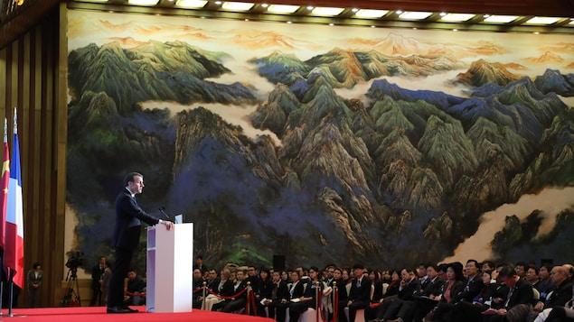 Le président Macron, debout devant un lutrin, parle aux nombreux invités conviés au palais impérial de Daming.