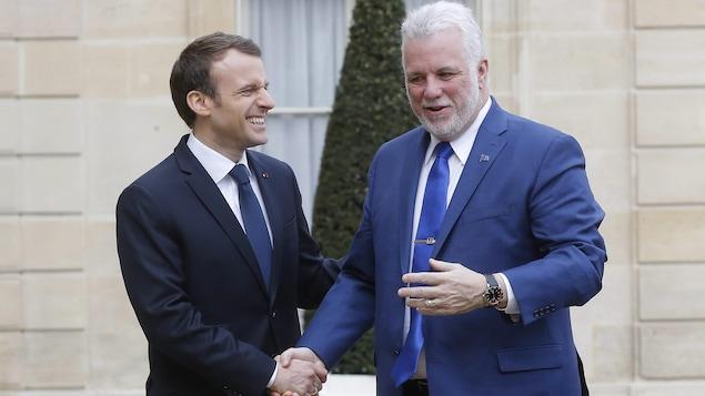 MM. Macron et Couillard échangent une poignée de main. Ils sont souriants.
