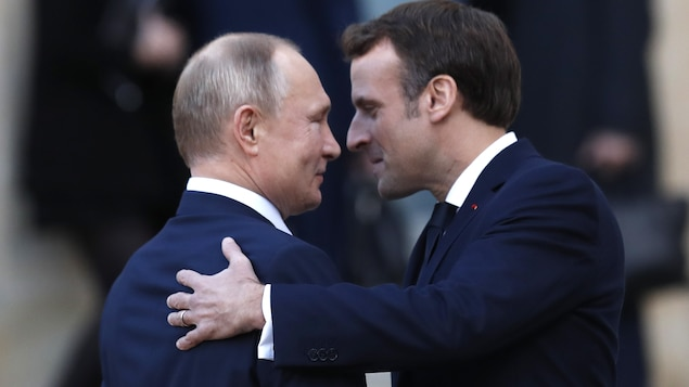 Emmanuel Macron et Vladimir Poutine se regardent dans les yeux. La main gauche de M. Macron est placée derrière l'épaule droite de son invité.
