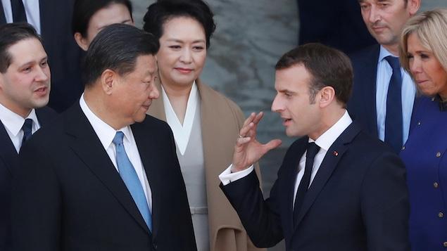 Xi Jinping et Emmanuel Macron discutent sous le regard de leurs épouses et d'autres diplomates.