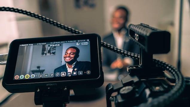 Un homme pose devant le une caméra.
