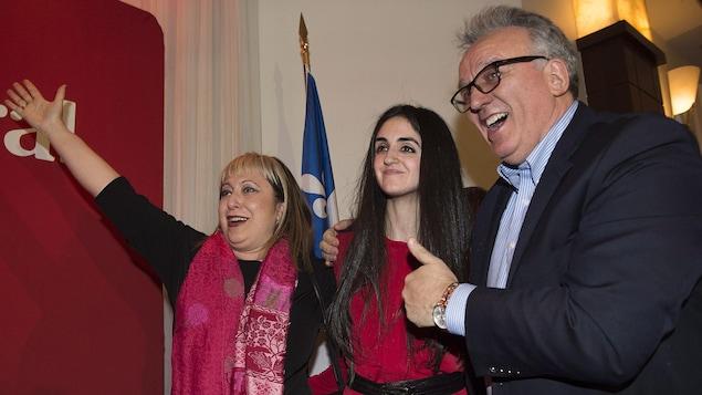 La candidate libérale Emmanuella Lambropoulos prend une photo avec deux personnes à ses côtés.