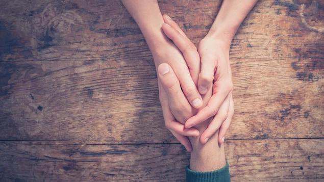 Une femme tient la main d'un homme entre ses mains sur une table.