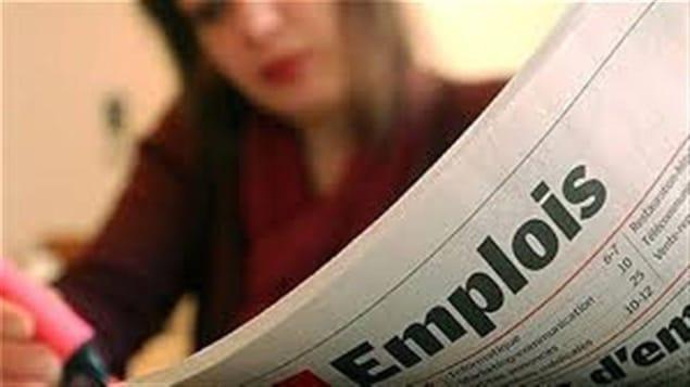 Une femme lit un journal avec des annonces d'emploi.