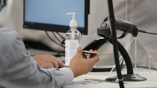 Un employé scanne la carte d'assurance maladie d'une personne qui sera vaccinée.