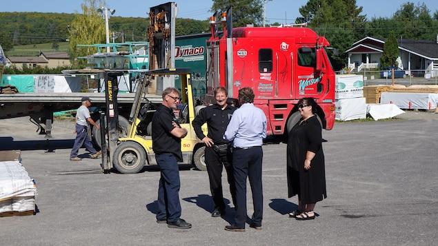 Quatre personnes dans une cour avec un camion