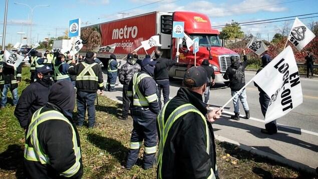Des syndiqués devant un camion de Metro.