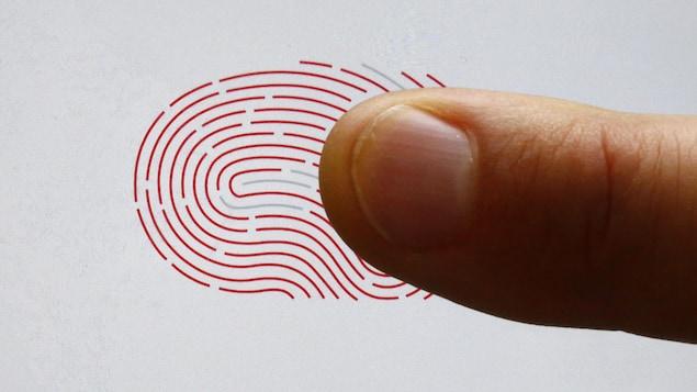 Une personne utilise un scanner biométrique avec son doigt.